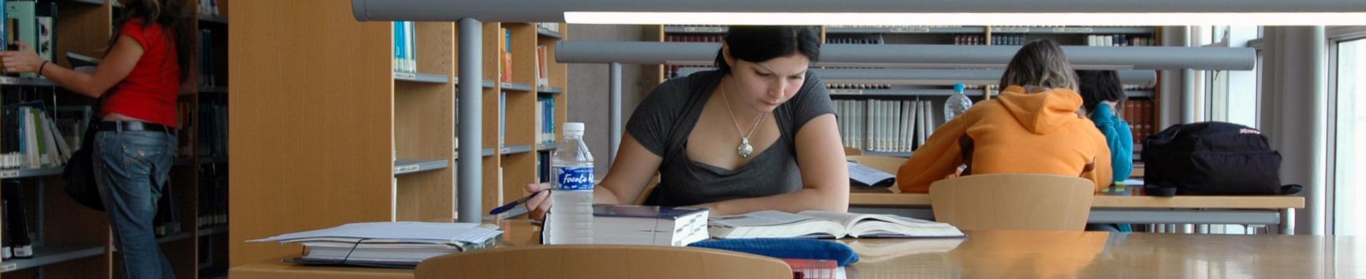 Vista del interior de una biblioteca luminosa con mujer estudiando en primer plano ante una mesa tomando notas ante libros. Al fondo, otras personas estudiando o de pie ante las estanterías.